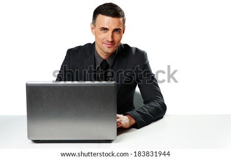 Smiling businessman sitting at the table with laptop isolated on a white background - stock photo