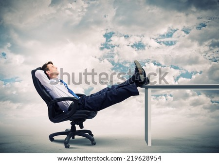 Smiling businessman sitting in chair with legs on table - stock photo