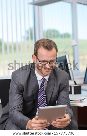 Smiling businessman sitting in his office reading his tablet computer with a large window with a rural view behind him - stock photo
