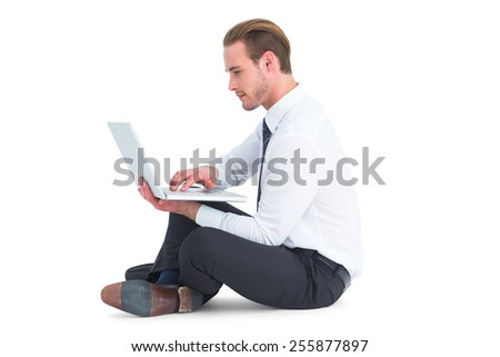 Smiling businessman sitting on floor using laptop on white background