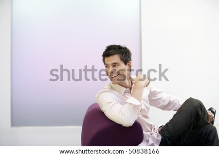 Smiling Businessman sitting on modern sofa, legs crossed, looking over shoulder