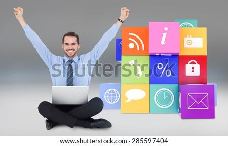Smiling businessman sitting on the floor cheering against grey vignette - stock photo