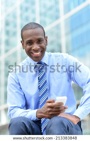 Smiling businessman sitting outdoors with cellphone - stock photo