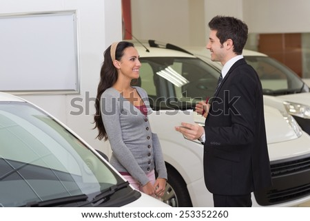Smiling businessman speaking with his customer at new car showroom - stock photo