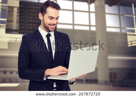 Smiling businessman standing and using laptop against airport - stock photo