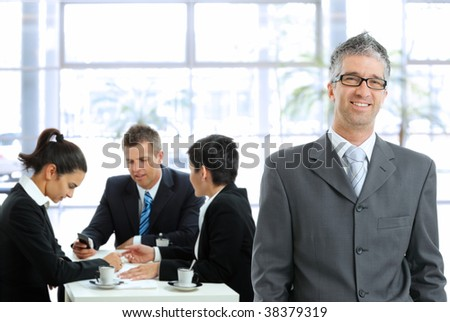 Smiling businessman standing in front, businesspeople talking at desk in the background.