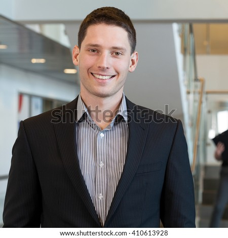 Smiling businessman standing in the office centre - stock photo