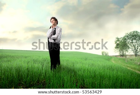 Smiling businessman standing on a green meadow