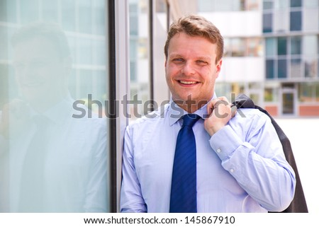 Smiling businessman standing outside a building