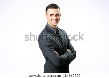 Smiling businessman standing with arms folded isolated on a white background - stock photo