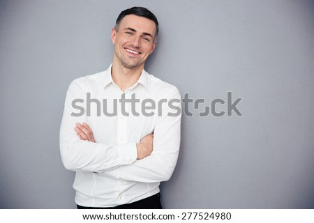 Smiling businessman standing with arms folded over gray background - stock photo