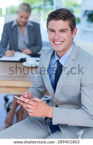 Smiling businessman texting on his mobile phone in an office