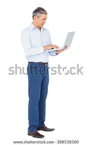 Smiling businessman typing on laptop on white background