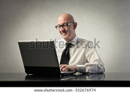 Smiling businessman using a pc - stock photo