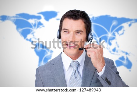 Smiling businessman using headset on world map background