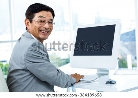 Smiling businessman using his computer in an office