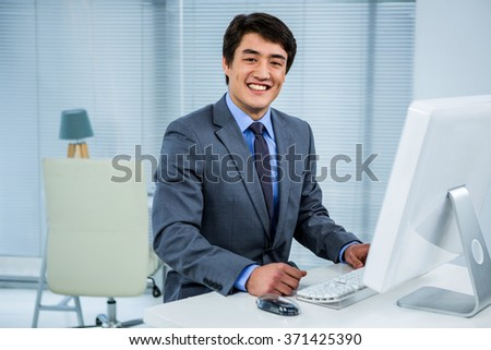 Smiling businessman using his computer in his office - stock photo