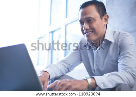 Smiling businessman using laptop in office - stock photo