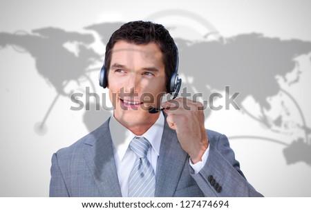 Smiling businessman wearing headset on world map background - stock photo