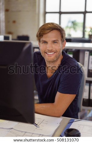 Smiling businessman wears casual attire in office and looks at camera by his computer