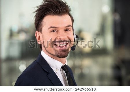 Smiling businessman with a headset is looking at the camera.