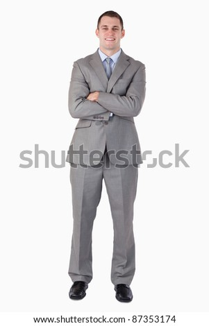 Smiling businessman with arms folded on white background