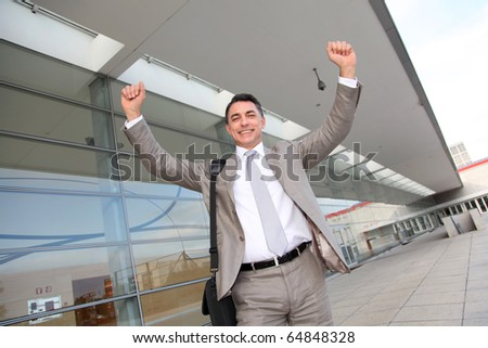 Smiling businessman with arms up - stock photo