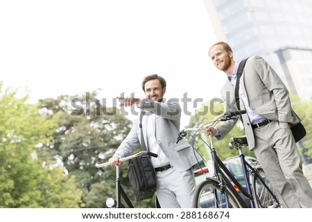 Smiling businessman with bicycle showing something to colleague on street - stock photo
