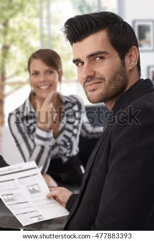 Smiling businessman with business report in hand looking at camera.