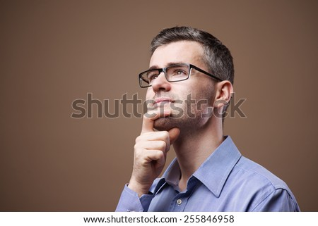Smiling businessman with hand on chin planning strategies and solutions - stock photo