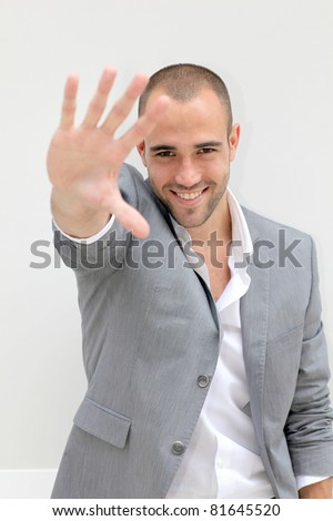 Smiling businessman with hand on foreground - stock photo