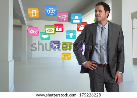 Smiling businessman with hand on hip against computing application icons