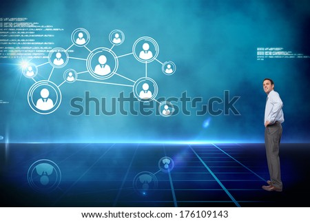 Smiling businessman with hand on hip against futuristic technology interface