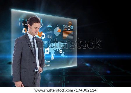Smiling businessman with hand on hip against keyhole on technological black background