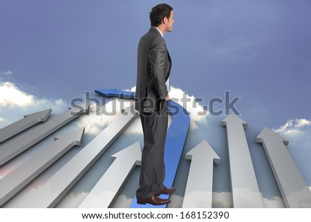 Smiling businessman with hand on hip against steps made from books