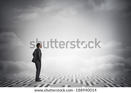 Smiling businessman with hands on hips against maze ending in cloudy sky