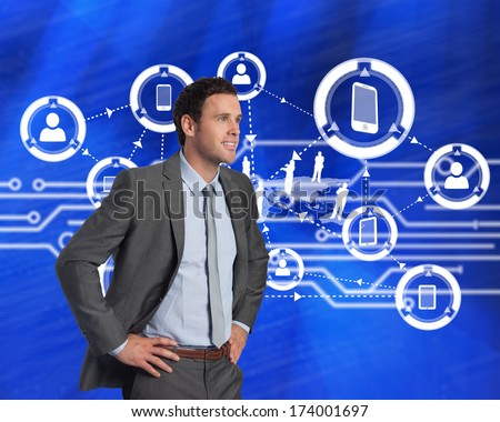 Smiling businessman with hands on hips against white circuit board on blue background