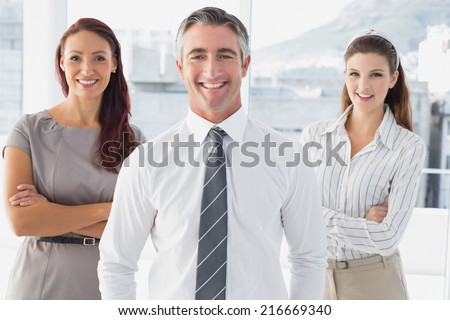 Smiling businessman with his co-workers in an office - stock photo