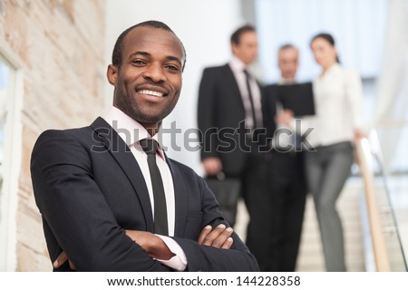 Smiling businessman with his colleagues in background