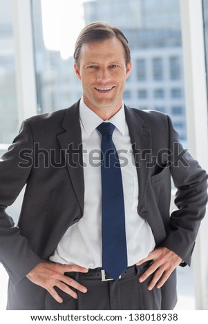 Smiling businessman with his hands on hips in his office - stock photo