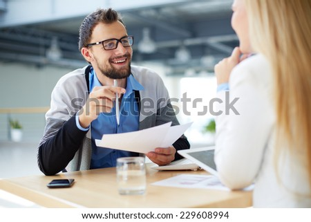 Smiling businessman with papers talking to female colleague - stock photo