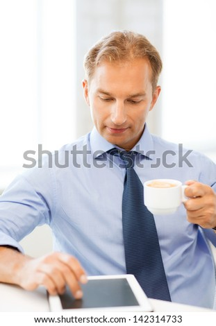 smiling businessman with tablet pc drinking coffee in office