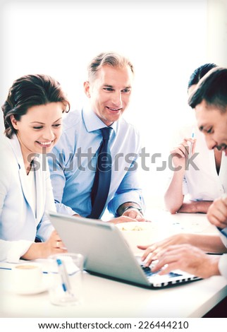 smiling businessman with team on meeting in office