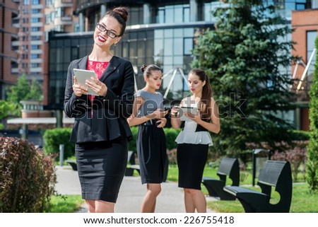 Smiling businessman working and holding a tablet on the street. Three girls businessmen or businesswomen holding tablets and looking in camera