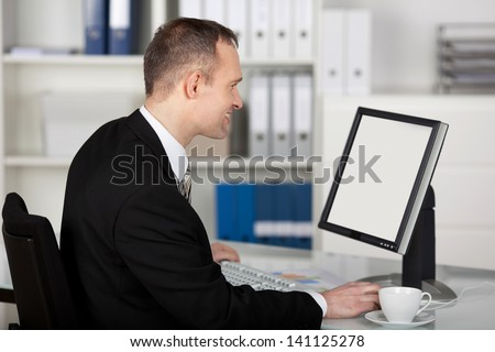 Smiling businessman working in front of computer at the office - stock photo