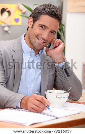 Smiling businessman working in his kitchen - stock photo