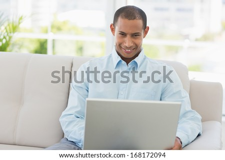 Smiling businessman working on laptop on the couch in the office