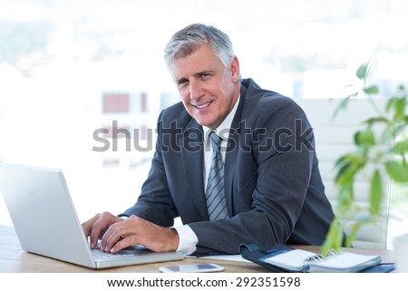 Smiling businessman working with his laptop in his office