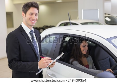 Smiling businessman writing on clipboard at new car showroom - stock photo