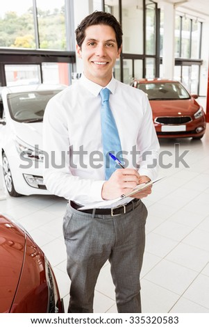 Smiling businessman writing on clipboard at new car showroom